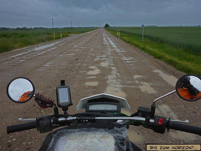 Feldweg mit Pfützen unter dunklen Wolken