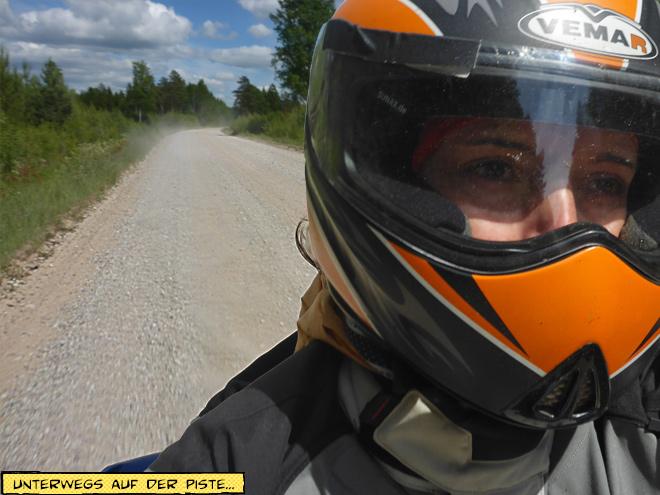 Motorradfahrerin auf Schotterpiste