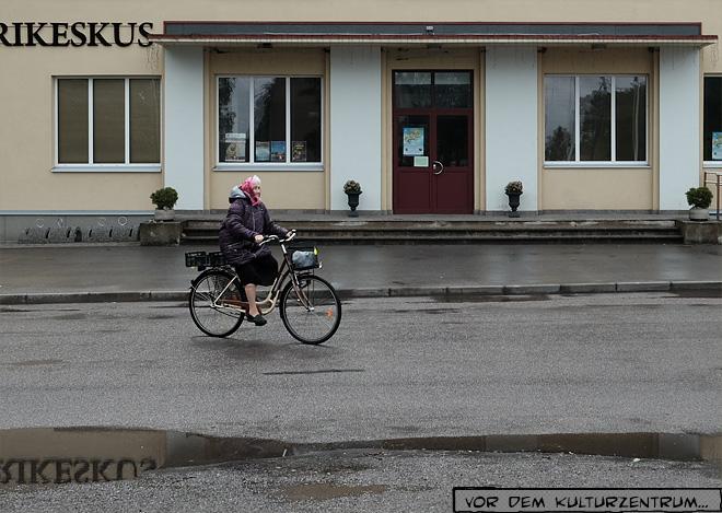 Alte Frau auf dem Fahrrad bei Regen