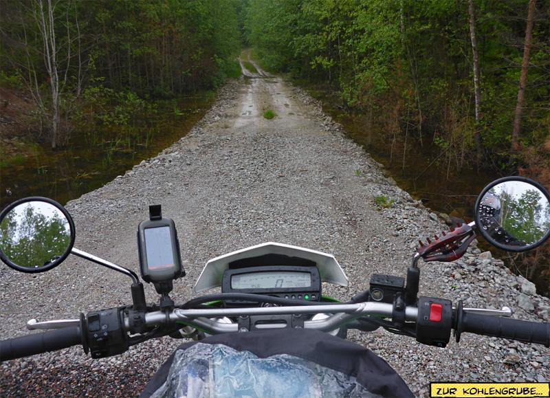 Waldweg auf dem Motorrad bei Regen