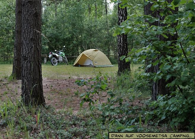 Zelt und Motorrad zwischen Bäumen