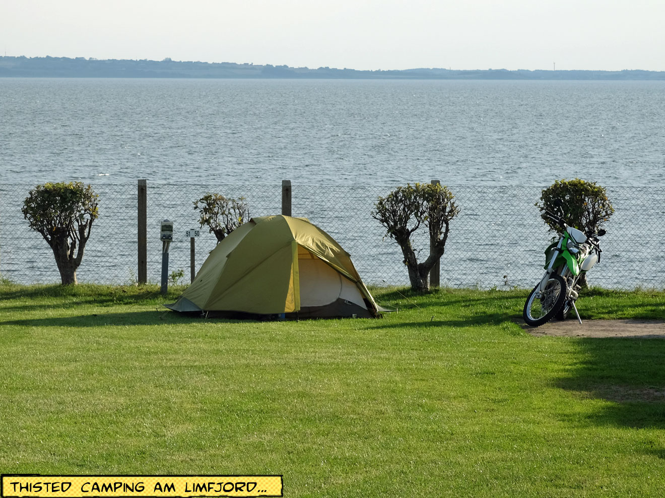 Zelt und Motorrad am Wasser