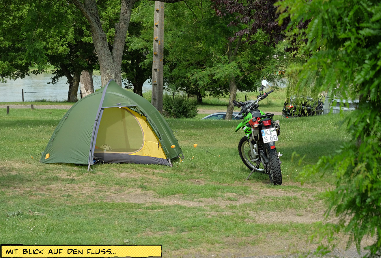 Zelt und Motorrad am Flussufer