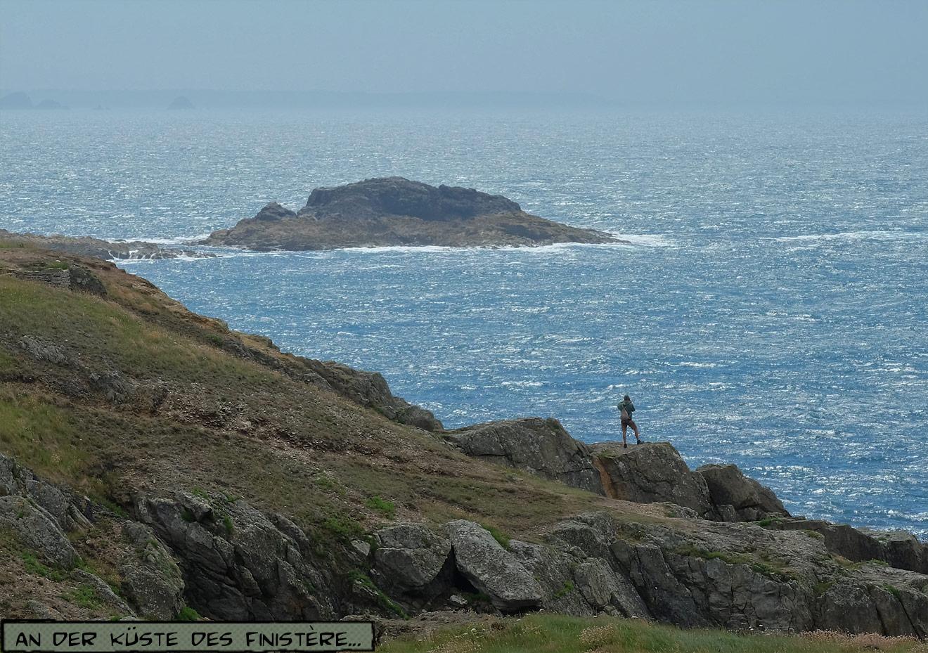 Mann steht auf Klippen über dem Meer