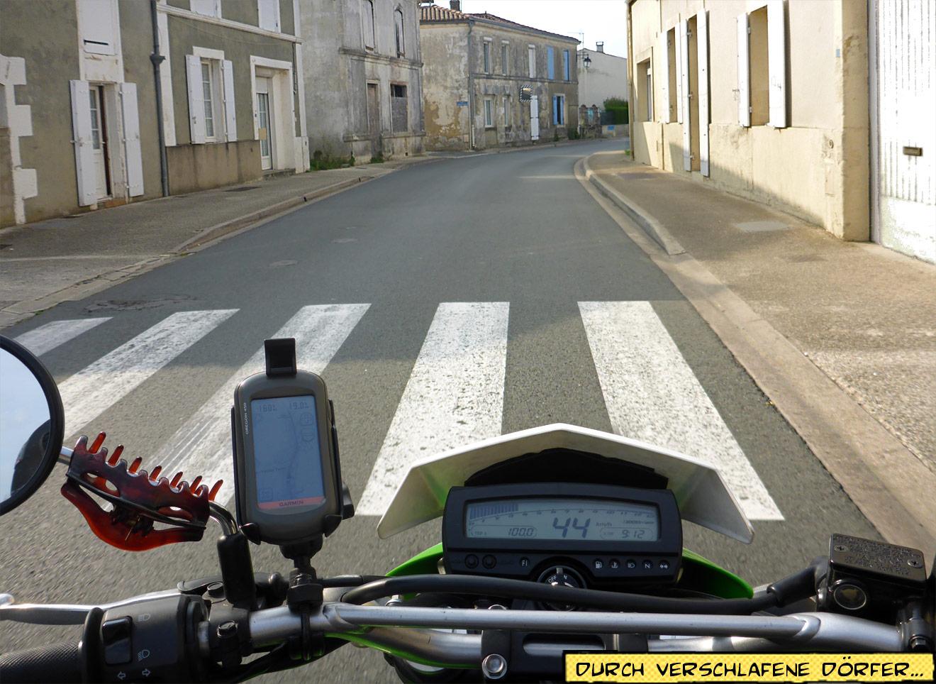 Motorrad fährt durch ein Dorf